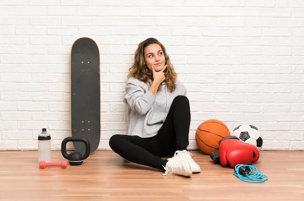 Giovane donna di sport che si siede sul pavimento che pensa un'idea