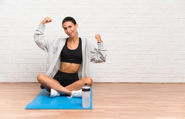 Giovane donna di sport che si siede sul pavimento con la stuoia che celebra una vittoria
