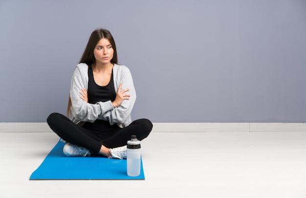 Giovane donna di sport che si siede sul pavimento con la stuoia che pensa un'idea