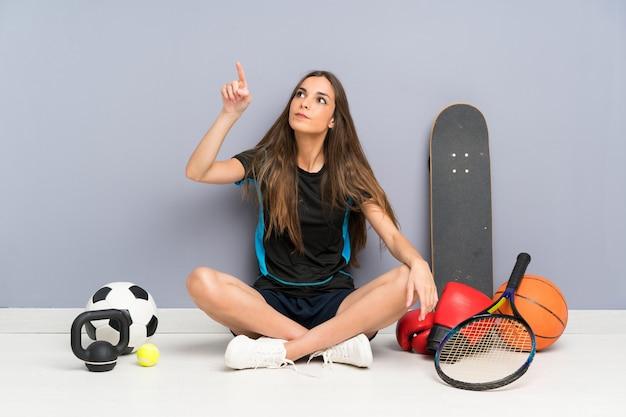 Giovane donna di sport che si siede sul pavimento toccando sullo schermo trasparente