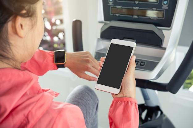 Giovane donna di sport che utilizza smart phone e orologio astuto in palestra