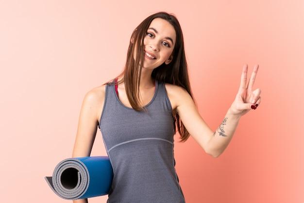 Giovane donna di sport con la stuoia sopra la parete isolata che sorride e che mostra il segno di vittoria