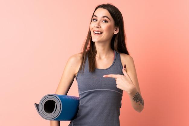 Giovane donna di sport con la stuoia sopra la parete isolata con espressione facciale di sorpresa