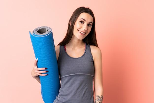 Giovane donna di sport con la stuoia sopra la parete isolata con l'espressione felice