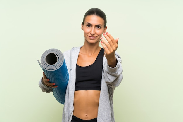 Giovane donna di sport con la stuoia sopra la parete verde isolata che invita a venire con la mano. felice che tu sia venuto
