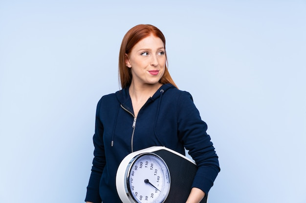 Giovane donna di sport della testarossa sopra la parete blu isolata con la pesa