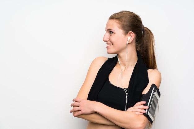 Giovane donna di sport sopra la parete bianca isolata che sta e che guarda al lato