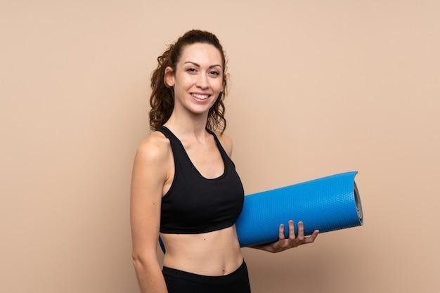Giovane donna di sport sopra la parete isolata con una stuoia e sorridere