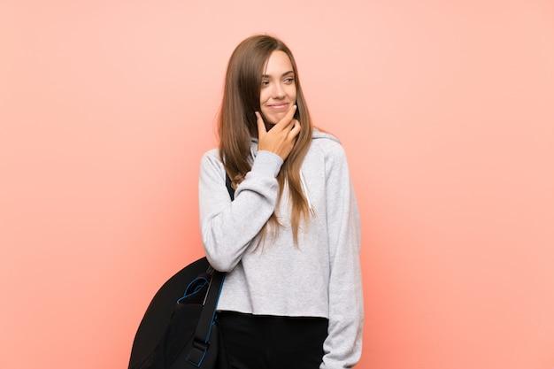 Giovane donna di sport sopra la parete rosa isolata che pensa un'idea