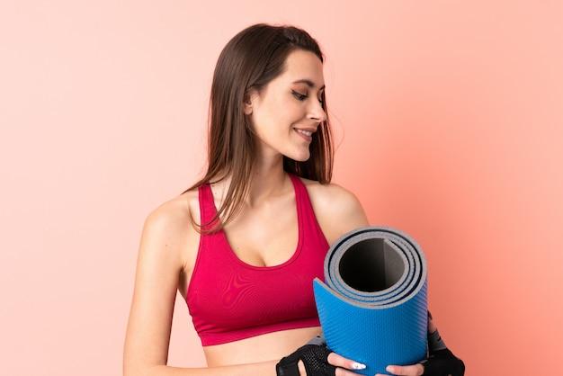Giovane donna di sport sopra la parete rosa isolata con una stuoia e sorridere