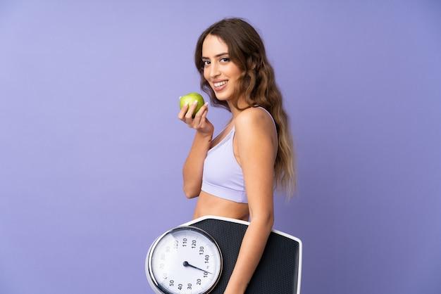 Giovane donna di sport sopra la parete viola isolata con la pesa e con una mela