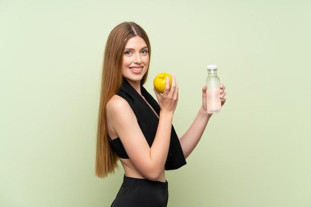 Giovane donna di sport sopra verde isolato con una mela