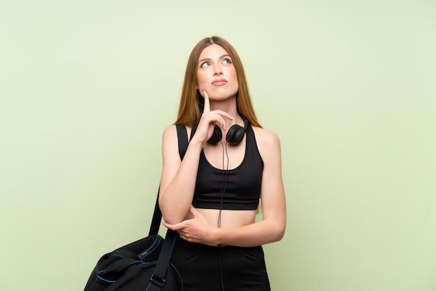 Giovane donna di sport su verde che pensa un'idea
