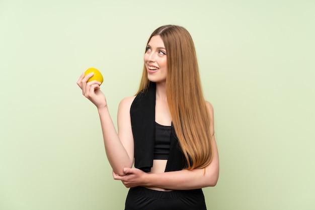 Giovane donna di sport su verde con una mela