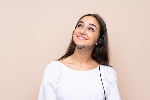 Giovane donna di telemarketer che osserva in su mentre sorridendo
