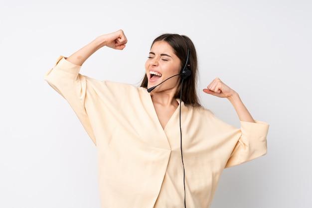 Giovane donna di telemarketer sopra bianco isolato che celebra una vittoria