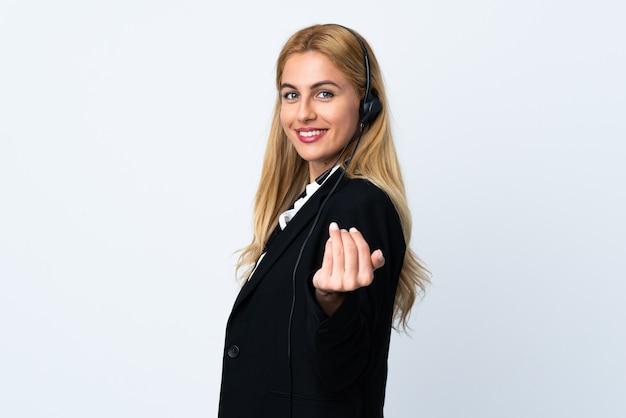 Giovane donna di telemarketer sopra la parete bianca che invita a venire con la mano. felice che tu sia venuto