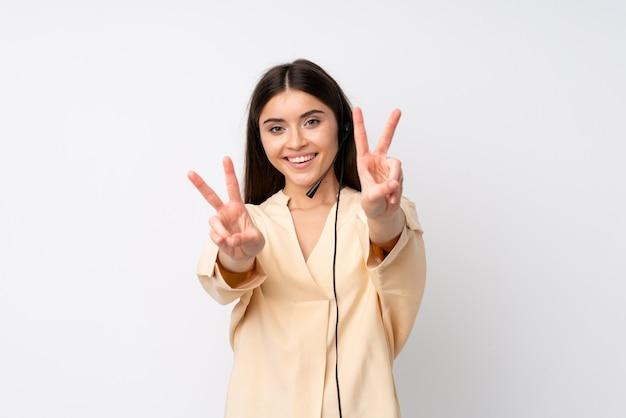Giovane donna di telemarketer sopra la parete bianca isolata che sorride e che mostra il segno di vittoria