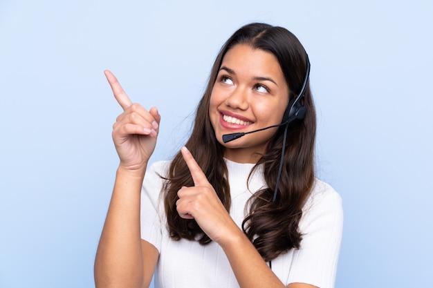 Giovane donna di telemarketer sopra la parete isolata