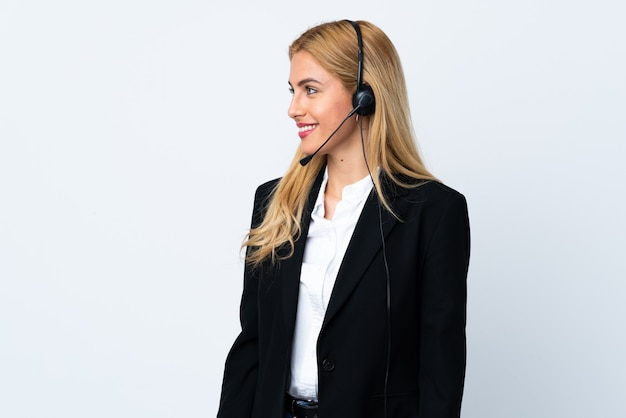 Giovane donna di telemarketer sopra spazio bianco isolato che sembra laterale