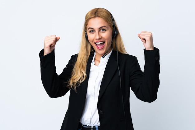 Giovane donna di telemarketer su bianco isolato che celebra una vittoria