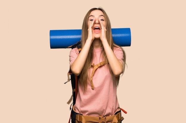 Giovane donna di viaggiatore con zaino e sacco a pelo che grida e che annuncia qualcosa sulla parete gialla isolata