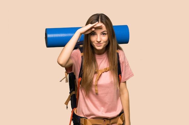 Giovane donna di viaggiatore con zaino e sacco a pelo che guarda lontano con la mano per guardare qualcosa su fondo giallo isolato