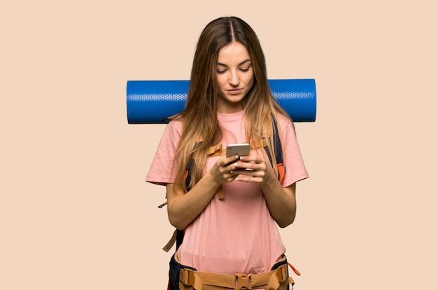 Giovane donna di viaggiatore con zaino e sacco a pelo che invia un messaggio con il cellulare sulla parete gialla isolata