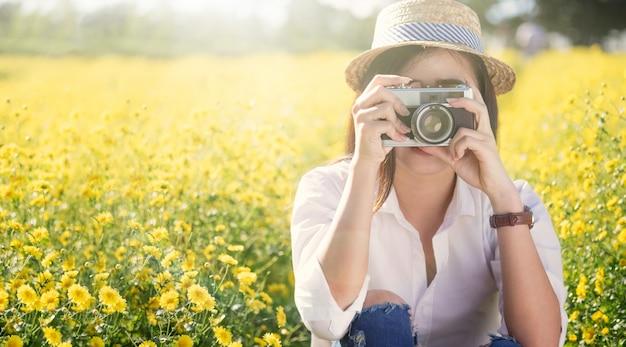 Giovane donna di viaggio in vacanza e utilizzando una fotocamera per scattare foto all'aperto al parco.