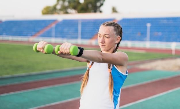 Giovane donna di vista frontale che fa esercizio delle mani