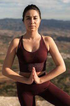 Giovane donna di vista frontale nella posa di yoga