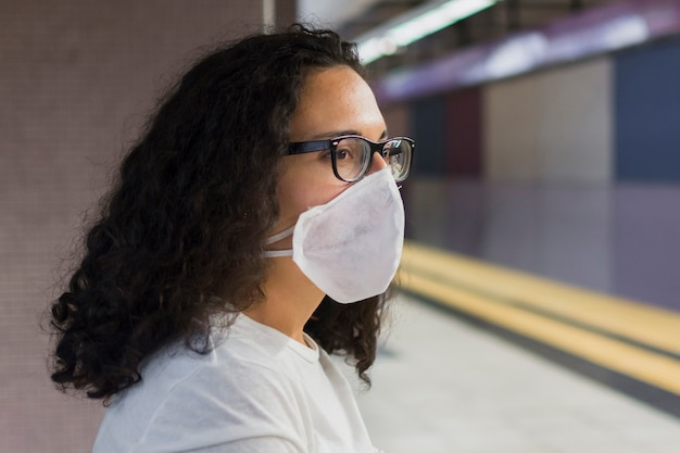 Giovane donna di vista laterale con l'attesa medica della maschera