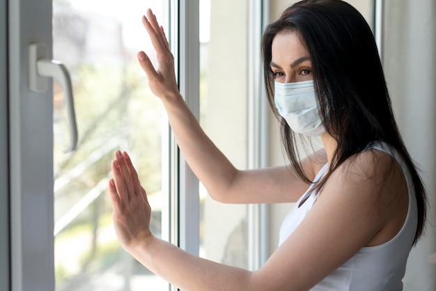 Giovane donna di vista laterale con la mascherina medica