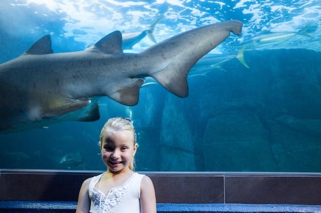 Giovane donna dietro un carro armato dello squalo che esamina macchina fotografica