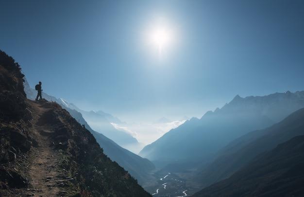Giovane donna diritta sulla collina e guardare sulla valle della montagna