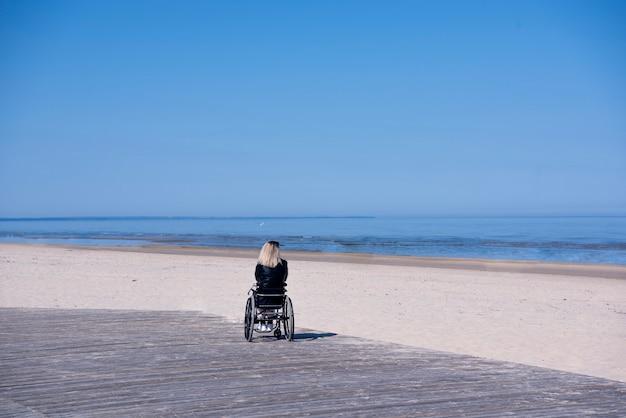 Giovane donna disabile sola sulla spiaggia. giornata di sole estivo.