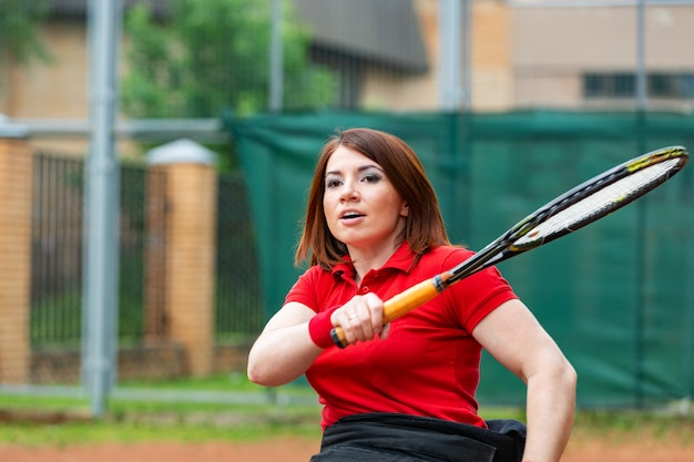 Giovane donna disabile sulla sedia a rotelle che gioca a tennis sul campo da tennis.