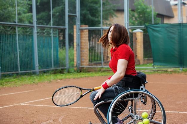 Giovane donna disabile sulla sedia a rotelle che gioca a tennis sul campo da tennis