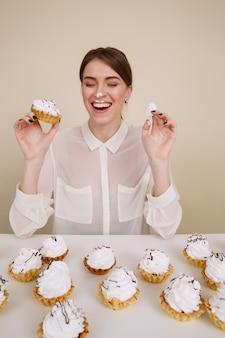 Giovane donna divertente allegra che mangia le torte e la risata