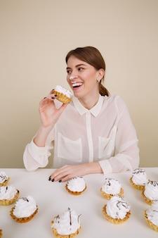 Giovane donna divertente felice che sorride e che mangia le torte