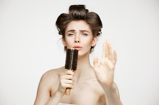 Giovane donna divertente in bigodini e asciugamano che si rallegra cantando in pettine. bellezza e spa.
