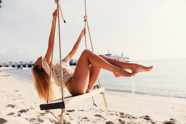 Giovane donna divertirsi sull'altalena