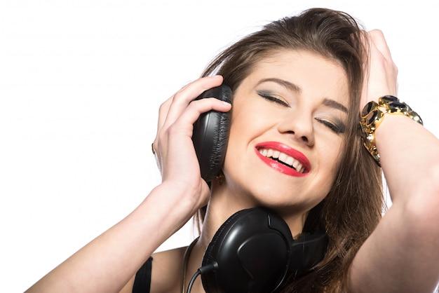 Giovane donna dj che gode della musica in cuffia.