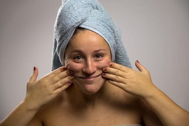 Giovane donna dopo la doccia con un asciugamano e sorridere. toccando il suo viso