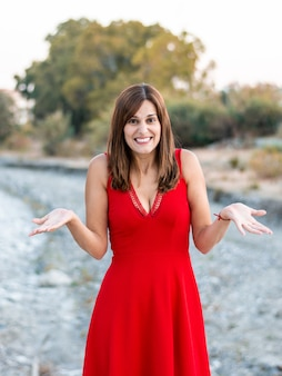 Giovane donna dubitando di cosa fare con un vestito rosso