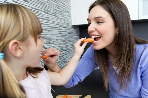 Giovane donna e bambina mangiare carote in cucina
