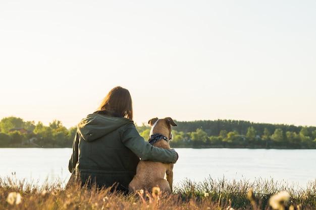 Giovane donna e cane vicino al lago al tramonto