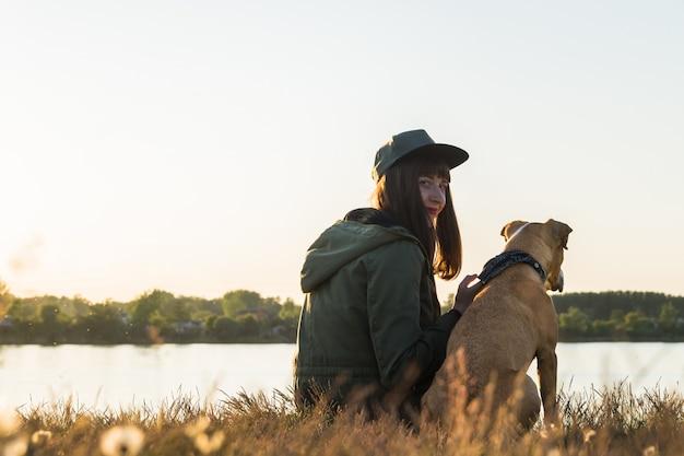 Giovane donna e il suo cane sul lago al tramonto