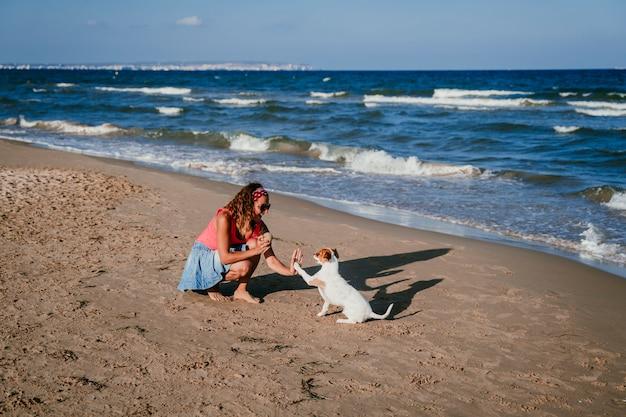 Giovane donna e il suo piccolo jack russell terrier sveglio che gioca alla spiaggia