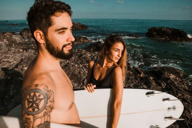 Giovane donna e ragazzo con tavole da surf sulla riva di roccia vicino mare